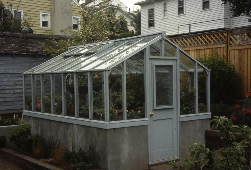 Redwood greenhouse on poured concrete wall