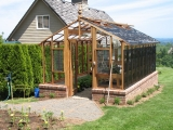 Tall redwood and glass greenhouse on brick base