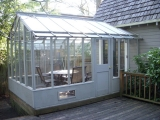Tall glass greenhouse attached at one end