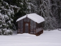 Redwood & glass greenhouse in snow