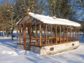 Tall redwood greenhouse in snow