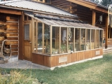 Garden sun room greenhouse attached to a log cabin