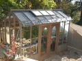 Tall wood greenhouse on a small patio