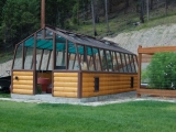 Redwood greenhouse with log base wall