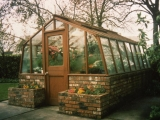 Glass greenhouse with brick base wall