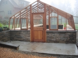 Large home greenhouse on stone base wall