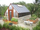 Tudor style home greenhouse with masonry base
