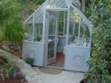 Small Tudor greenhouse that is stained gray