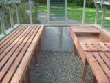 Redwood greenhouse interior with garden bench
