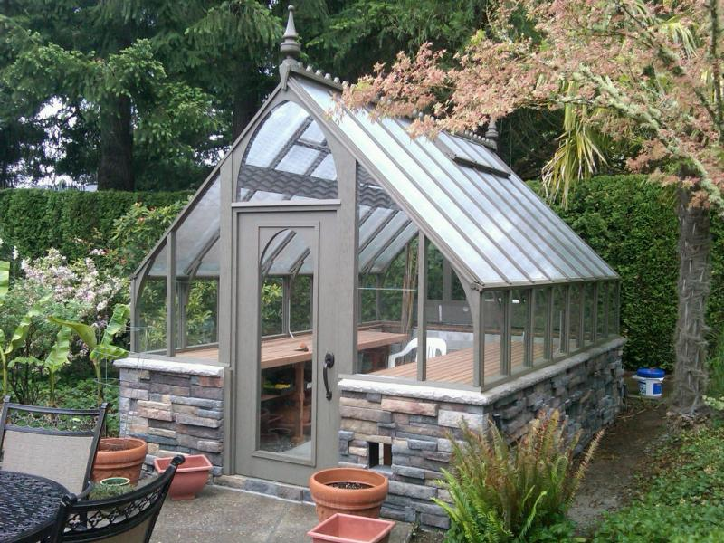Redwood greenhouse stained gray with stone base