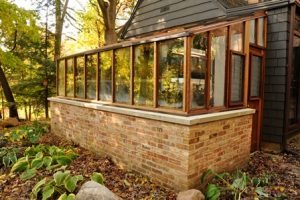 This energy efficient greenhouse has a brick base for thermal mass. Attachment to the house also helps with efficiency.